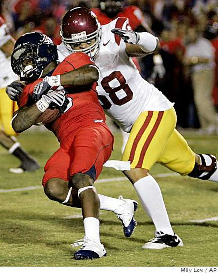 Arizona's Nic Grigsby, left, is caught from behind by Southern California's Rey Maualuga (58) in the first half of an NCAA college football game at Arizona Stadium in Tucson, Ariz., Saturday, Oct. 25, 2008. (AP Photo/Wily Low) Photo: Wily Low, AP