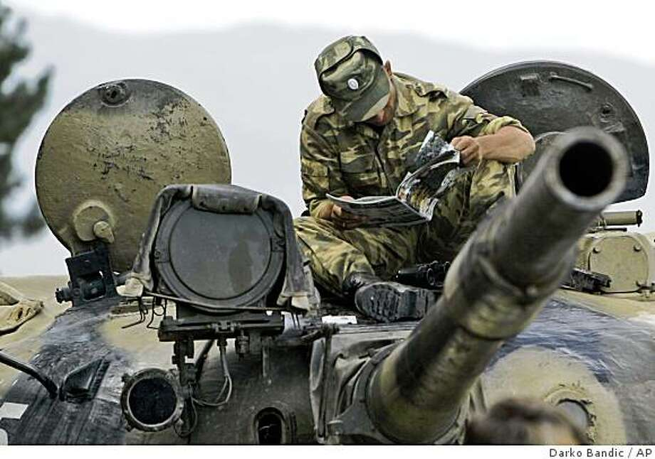 A Russian soldier reads atop of a tank at a checkpoint on the outskirts of Gori, northwest of the capital Tbilisi, Georgia, Friday, Aug. 15, 2008. Western leaders engaged in intense diplomacy Friday to persuade Russia to pull troops out of Georgia, but regional tensions soared after a top Russian general warned that Poland could face attack over its missile defense deal with the United States. (AP Photo/Darko Bandic) Photo: Darko Bandic, AP