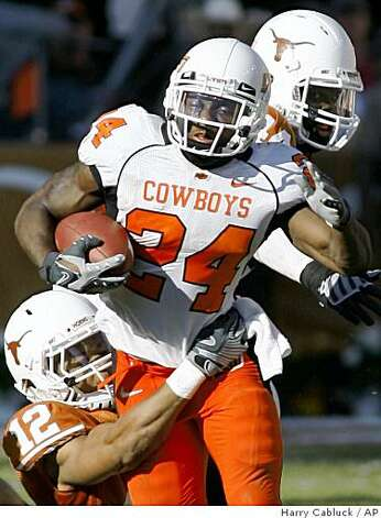 Oklahoma State running back Kendall Hunter is stopped by Texas safety Earl Thomas, left, during third-quarter NCAA college football action Saturday, Oct. 25, 2008, in Austin, Texas. Hunter took the shovel pass from quarterback Zac Robinson and advanced the ball 31 yards to the OSU 47-yard line. Hunter rushed for 161 yards in the game. Texas won it 28-24. Texas linebacker Rashad Bobino is in the background. (AP Photo/Harry Cabluck) Photo: Harry Cabluck, AP