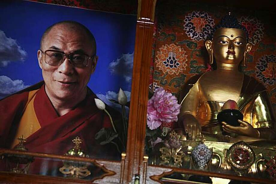 In this May 10, 2010, photograph, a photograph of Tibetan spiritual leader the Dalai Lama sits next to a statue of Buddha at the Nechung Dorje Drayangling Monastery in Dharamsala, Himachal Pradesh, northern India. As the Dalai Lama, the center of the Tibetan exile movement approaches his 75th birthday, the question has become impossible to escape: What happens when he dies? Photo: Kevin Frayer, AP