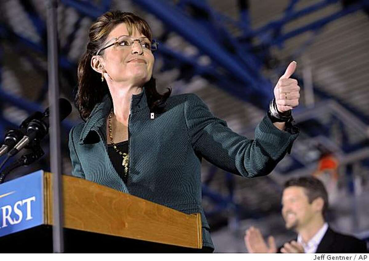 Republican vice presidential candidate, Alaska Gov. Sarah Palin, left, along with her husband Todd Palin attend a rally at Marietta Collage Sunday, Nov. 2, 2008 in Marietta, Ohio. (AP Photo/Jeff Gentner)