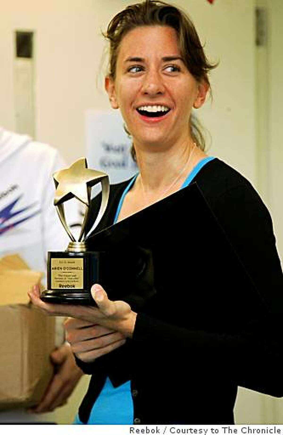 Arien O'Connell accepts a trophy In New York from the Reebok company in recognition of running the fastest time at the San Francisco Nike Women's Marathon.