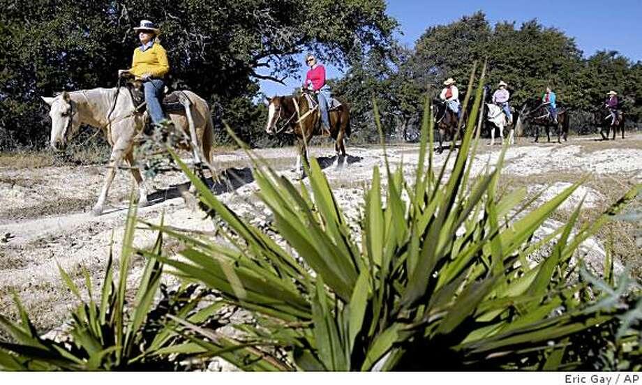 Visitors take a morning ride at the Dixie Dude Ranch near Bandera, Texas, Friday, Oct. 24, 2008.  (AP Photo/Eric Gay) Photo: Eric Gay, AP