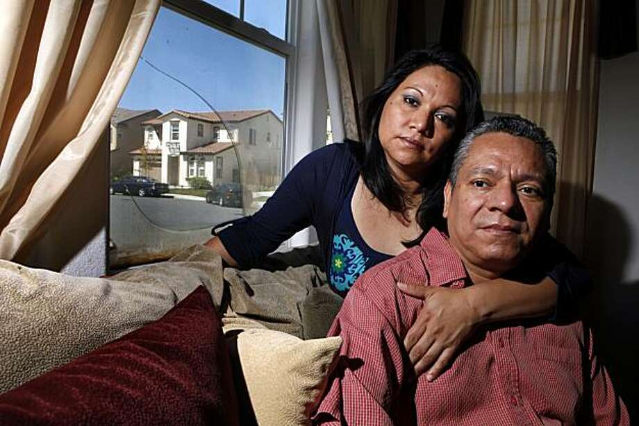 Jose and Lucy Vega sit in their foreclosed living room of their Pittsburg home. Jose was on the phone talking with his lender, Chase Bank, about his loan modification when a real estate agent knocked on the door and told him his house had already been foreclosed on. Photo:  Lance Iversen, The Chronicle
