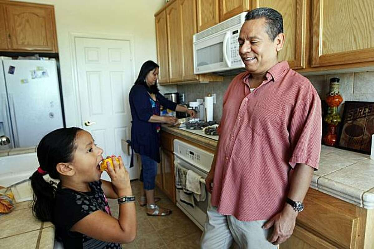 Jose and Lucy Vega prepare fruit snacks for their daughter Luciana age 5 in their foreclosed Pittsburg home Saturday May 29, 2010. Jose was on the phone talking with his lender, Chase Bank about his loan modification when a real estate agent knocked on the door and told him his house had already been foreclosed on. A proposed California bill seeks to prevent such situations by requiring lenders to give a decision on loan mods before starting foreclosure proceedings.