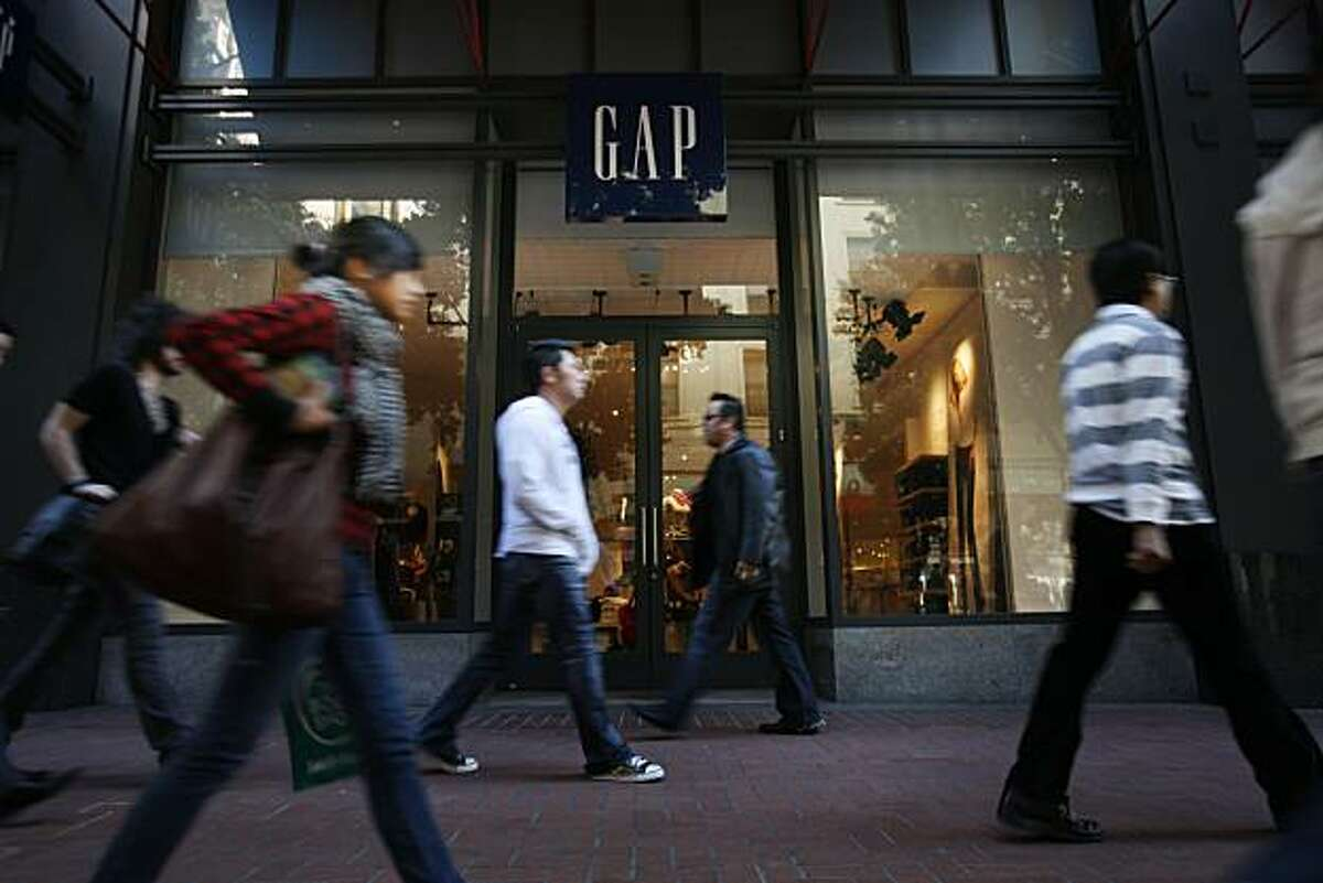 Shoppers and tourists walk past the Gap store at Powell and Market Streets on Thursday Nov. 6, 2008 in San Francisco, Calif. Octobers has been a below average month for retail.