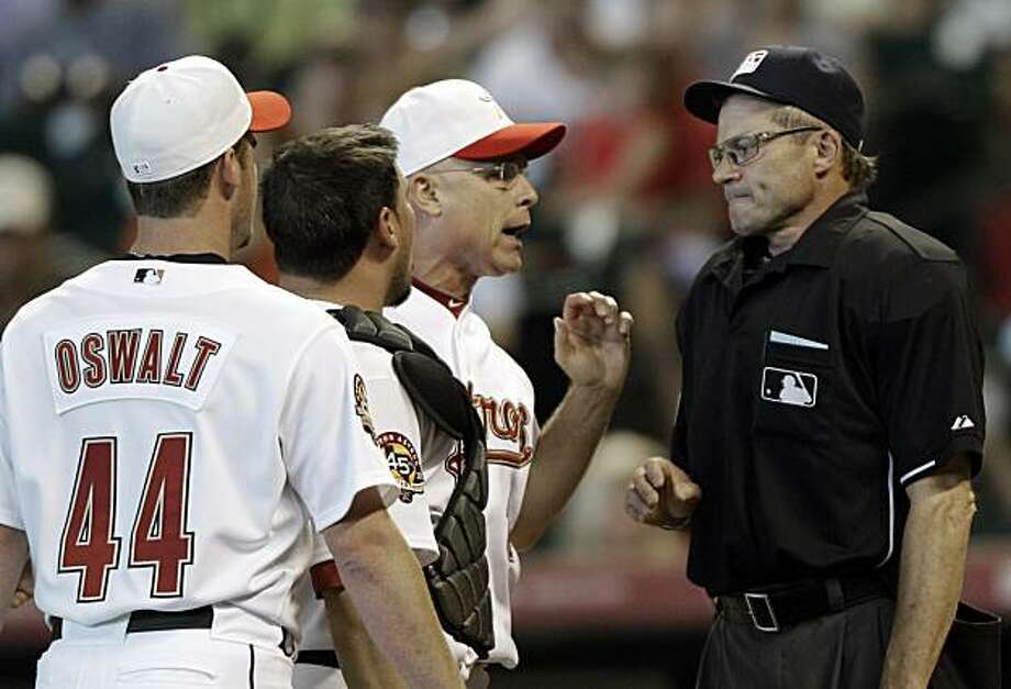 Home plate umpire Bill Hohn, right, listens to Houston Astros manager Brad Mills, center, after ejecting starting pitcher Roy Oswalt (44) during the third inning of a baseball game against the Washington Nationals Monday, May 31, 2010 in Houston. Photo: David J. Phillip, AP