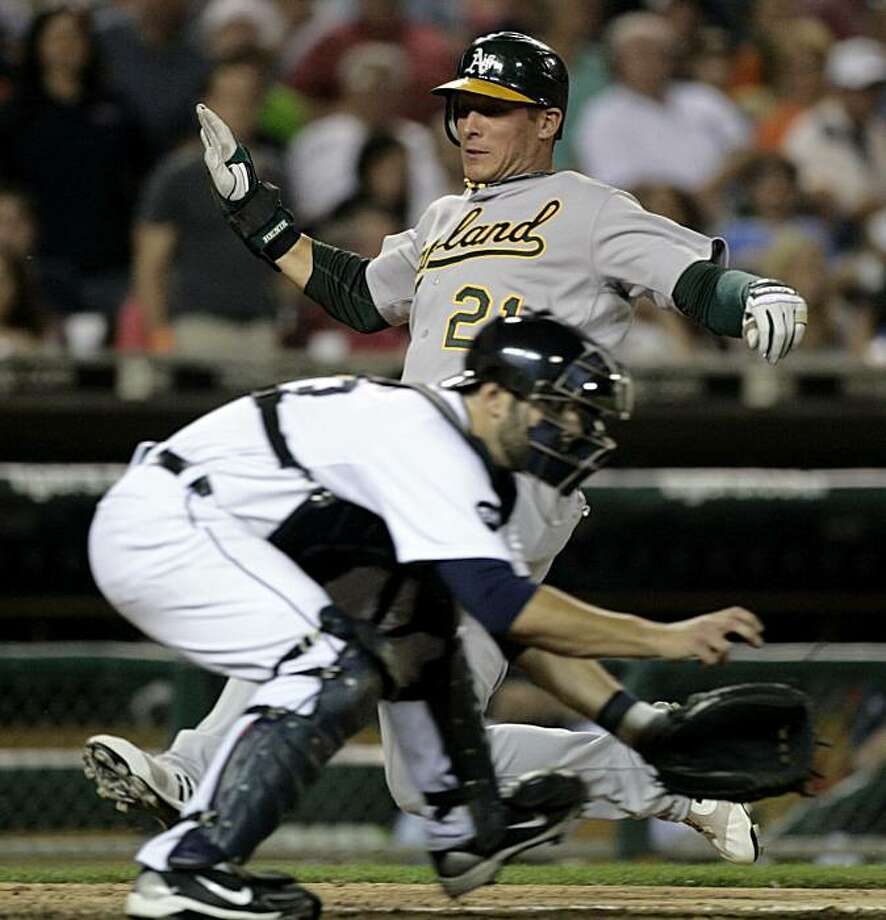 Oakland Athletics' Ryan Sweeney, rear, scores past Detroit Tigers catcher Alex Avila on a sacrifice fly ball by Oakland's Landon Powell in the ninth inning of a baseball game Friday, May 28, 2010, in Detroit. Sweeney's run was the game-winner in a 5-4 victory over the Tigers. Photo: Duane Burleson, AP