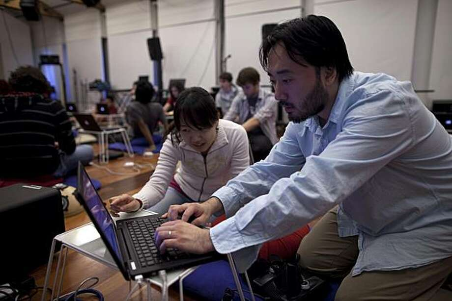 Ge Wang, Director and assistant professor helps co-director Jienun Oh reseting a computer as members of the Stanford Computer-Music centers project called SLORK, the Stanford Laptop Orchestra rehearse at the CCRMA Stage at Stanford University on May 28, 2010 in Stanford, Calif. Photograph by David Paul Morris/Special to the Chronicle Photo: David Paul Morris, Special To The Chronicle