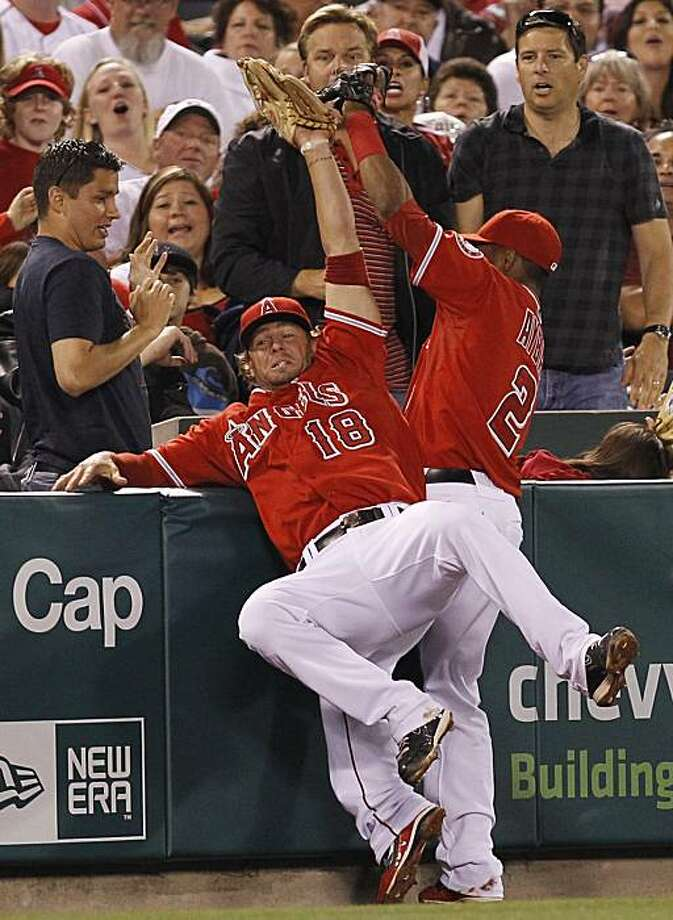 Los Angeles Angels third baseman Kevin Frandsen, left, catches a fly ball in the stands hit by Seattle Mariners' Mike Sweeney as shortstop Erick Aybar also attempts to catch it to end the top of the fifth inning of a baseball game, Friday, May 28, 2010, in Anaheim, Calif. Photo: Danny Moloshok, AP
