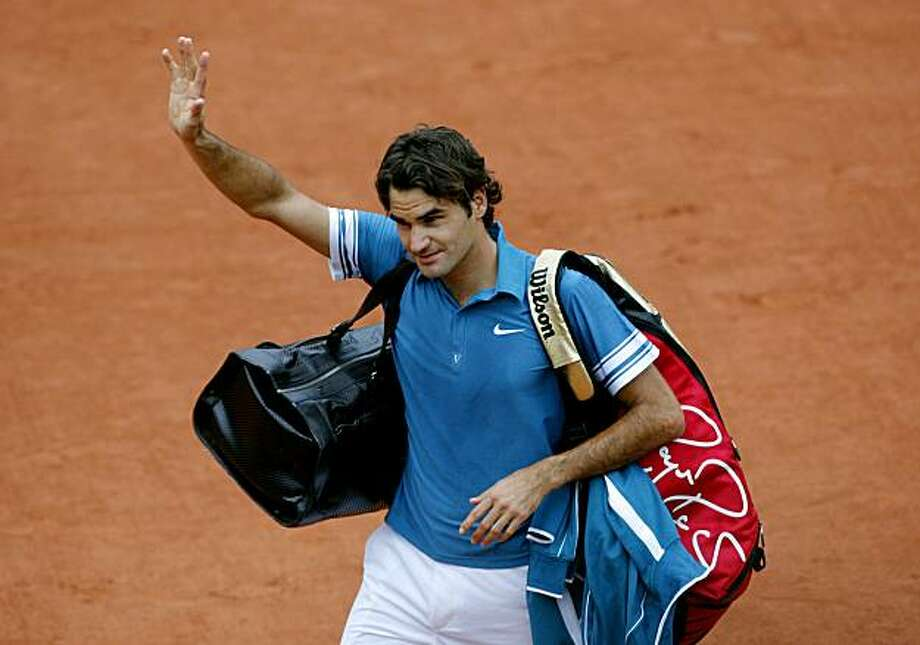 Switzerland's Roger Federer waves as he walks off the court after being defeated by Sweden's Robin Soderling during a quarter final match for the French Open tennis tournament at the Roland Garros stadium in Paris, Tuesday, June 1, 2010. Photo: Christophe Ena, AP