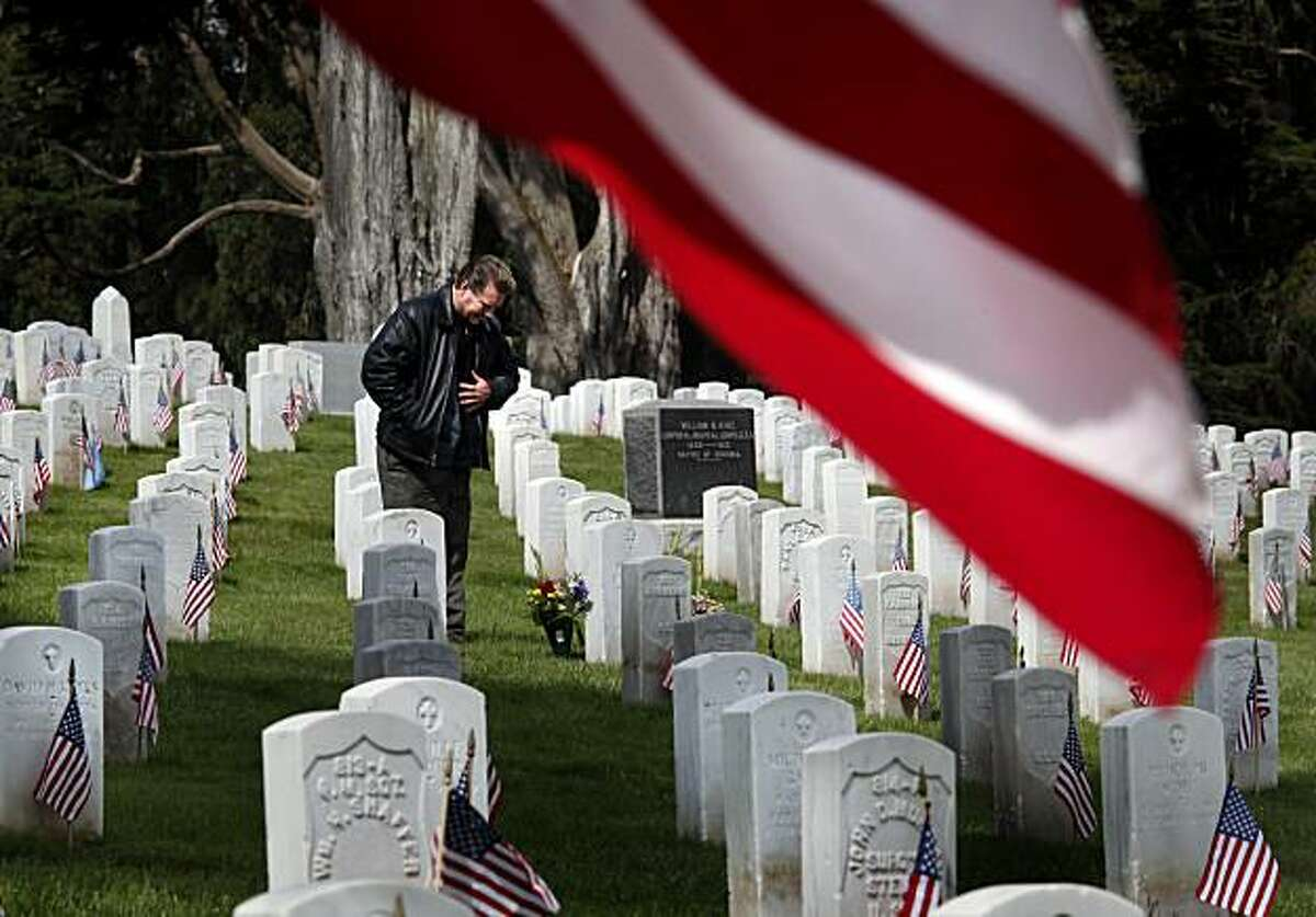 Michael Timboe pauses at the grave sites of his father, who was killed in Vietnam, and grandfather, after laying flowers at the San Francisco National Cemetery, Monday, May 31, 2010, in San Francisco. The annual Memorial Day ceremony in the Presidio drew hundreds of veterans and others. (AP Photo/San Francisco Chronicle, Brant Ward) NORTHERN CALIFORNIA MANDATORY CREDIT PHOTOG & CHRONICLE; MAGS OUT; NO SALES