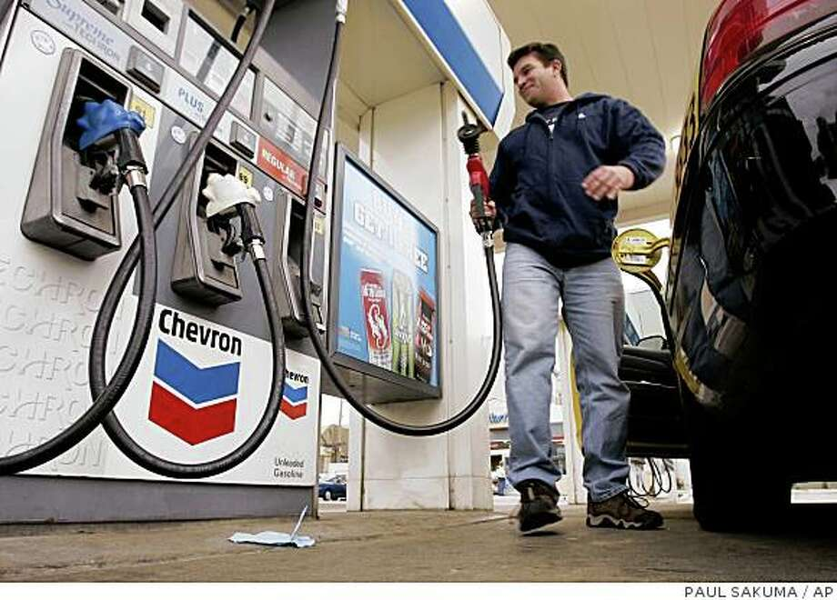 ** FILE ** Taxi cab driver Fred Costa finishes pumping gas at a Chevron gas station in San Francisco in this Feb. 1, 2007 file photo. Chevron Corp. said Friday, Nov. 2, 2007 its third-quarter profit plunged even further than analysts feared, driven by the second largest U.S. oil company's inability to recover its higher refining costs at the gasoline pump. (AP Photo/Paul Sakuma, file) Ran on: 11-03-2007 Higher crude oil prices squeezed the profit Chevron made from selling gasoline and diesel.** FILE ** Taxi cab driver Fred Costa finishes pumping gas at a Chevron gas station in San Francisco in this Feb. 1, 2007 file photo. Chevron Corp. said Friday, Nov. 2, 2007 its third-quarter profit plunged even further than analysts feared, driven by the second largest U.S. oil company's inability to recover its higher refining costs at the gasoline pump. (AP Photo/Paul Sakuma, file) Photo: PAUL SAKUMA, AP