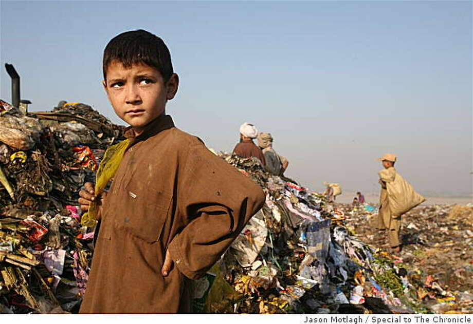 Afghan boy takes a break from scavenging at the city dump, Lahore. Photo: Jason Motlagh, Special To The Chronicle