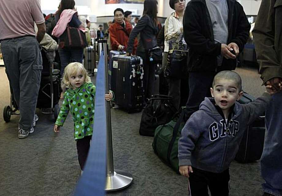 Headed east for weekend holiday events, Charlotte Quigley, 2, of San Francisco and Yusef Ziadeh, 2, of Modesto, join other pre-Memorial Day travelers waiting in line in the SFO domestic terminal on Wednesday May 26, 2010 in South San Francisco, Calif. Lines may be longer than usual this holiday because air travel is expected to be up by 5 percent of last year. Photo: Mike Kepka, The Chronicle