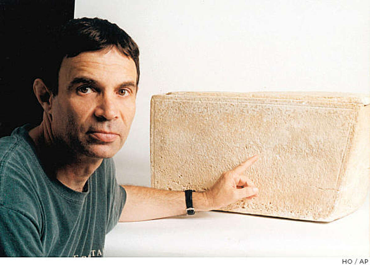 Antiquities collector Oded Golan, an engineer from Tel Aviv, points to an inscription on a burial box he owns in this Oct. 2002 file photo. The inscription reads: James, son of Joseph, brother of Jesus, and led some scholars to believe it contained the remains of James, the brother of Jesus of Nazareth. Others have said it might be a forgery, or that it might have been the burial box of a different James, unrelated to the biblical Jesus.(AP Photo/HO) ** ISRAEL