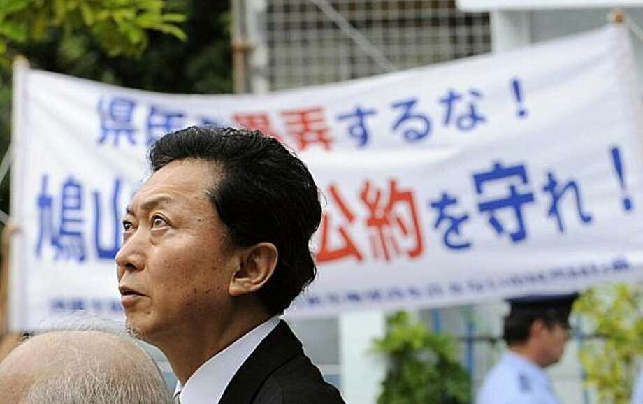 "Japanese Prime Minister Yukio Hatoyama raises his head skyward as he passes by a banner reading ""Keep the promise"" in Naha during his tour to Okinawa, southern Japan, Sunday, May 23, 2010. Hatoyama apologized Sunday to the people of Okinawa for ditching his campaign promise to move a U.S. military base off the island, a concession likely to further erode his grip on power. During his party's campaign for last year's elections that swept him to power, Hatoyama had promised to relocate U.S. Marine Corps' Futenma Air Station off Okinawa, perhaps even out of Japan. Photo: AP"