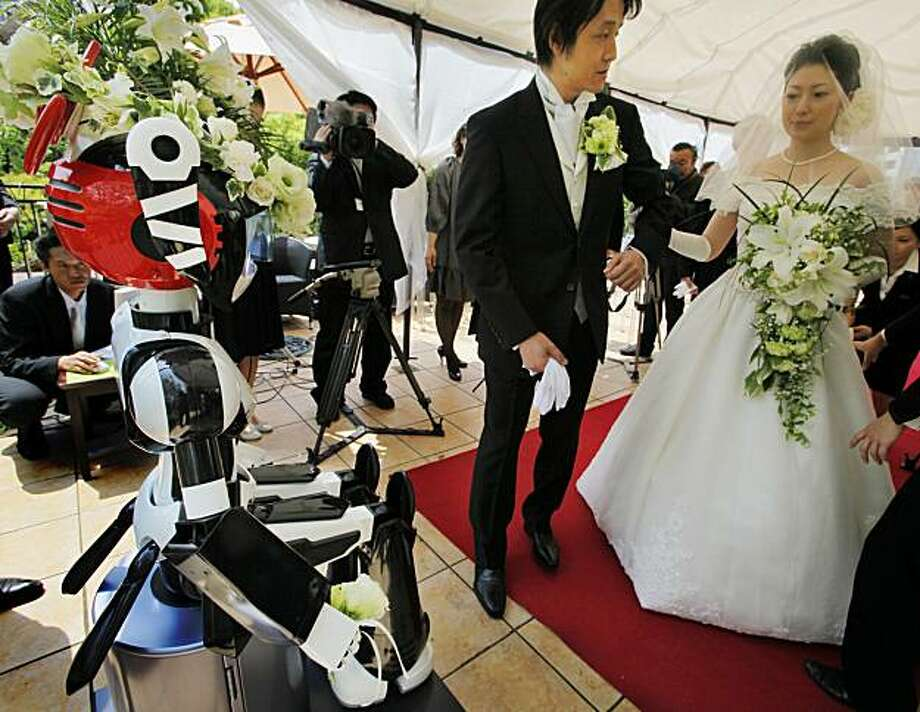I-Fairy, left, a four-foot tall seated robot with flashing eyes and plastic pigtails, directs a wedding ceremony for groom Tomohiro Shibata 42, and bride Satoko Inouye, 36, at a Tokyo restaurant Sunday, May 16, 2010. The wedding was the first time a marriage had been led by a robot, according to manufacturer Kokoro Co. Photo: Itsuo Inouye, AP
