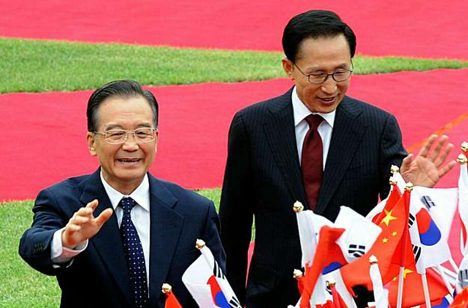 SEOUL, SOUTH KOREA - MAY 28:  Chinese Premier Wen Jiabao (L) and South Korean president Lee Myung-Bak (R) greet South Korean children during a welcoming ceremony held at the presidential House on May 28, 2010 in Seoul, South Korea. Wen is on tour to SouthKorea and Japan to seek the stability in the regions. Photo: Pool, Getty Images