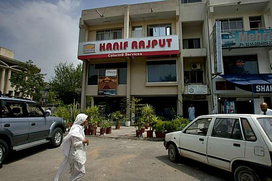 A woman walks past the main office of Hanif Rajput Catering Services in Islamabad, Pakistan, Saturday, May 22, 2010. Salman Ashraf Khan, co-owner of the catering company, who was among six men apparently detained by Pakistan for allegedly helping the Times Square bombing suspect, had differences with American policy in the region but no hatred toward the country, his father said. (AP Photo/Anjum Naveed) Photo: Anjum Naveed, AP