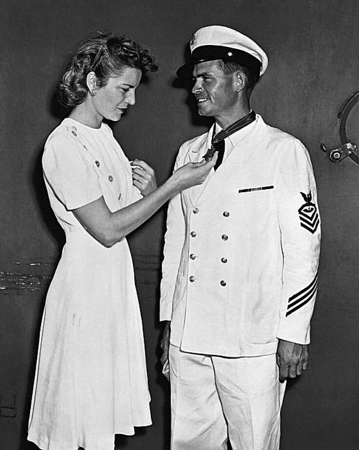 FILE - In this Sept. 28, 1942 photo provided by the U.S. Navy, Chief Ordnanceman John W. Finn is congratulated by his wife Alice at Pearl Harbor, Hawaii, after he was awarded the Congressional Medal of Honor or heroism at Kaneohe Naval Air Station for hisactions during the attack on Pearl Harbor. Finn, the oldest Medal of Honor recipient from World War II, died Thursday May 27, 2010 at his San Diego-area home at age 100. Photo: U.S. Navy, File, AP