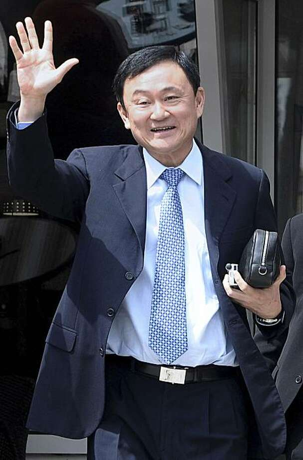 In this April 26, 2010 file photo, former Thai Prime Minister Thaksin Shinawatra waves as he walks out of a bank in Podgorica, Montenegro.  A Thai court issued an arrest warrant Tuesday May 25, 2010, for the ousted prime minister on terrorism charges, accusing the fugitive former leader of fomenting two months of unrest in Bangkok that left 88 people dead. If found guilty of the charges, he could face the death penalty. Photo: Risto Bozovic, AP