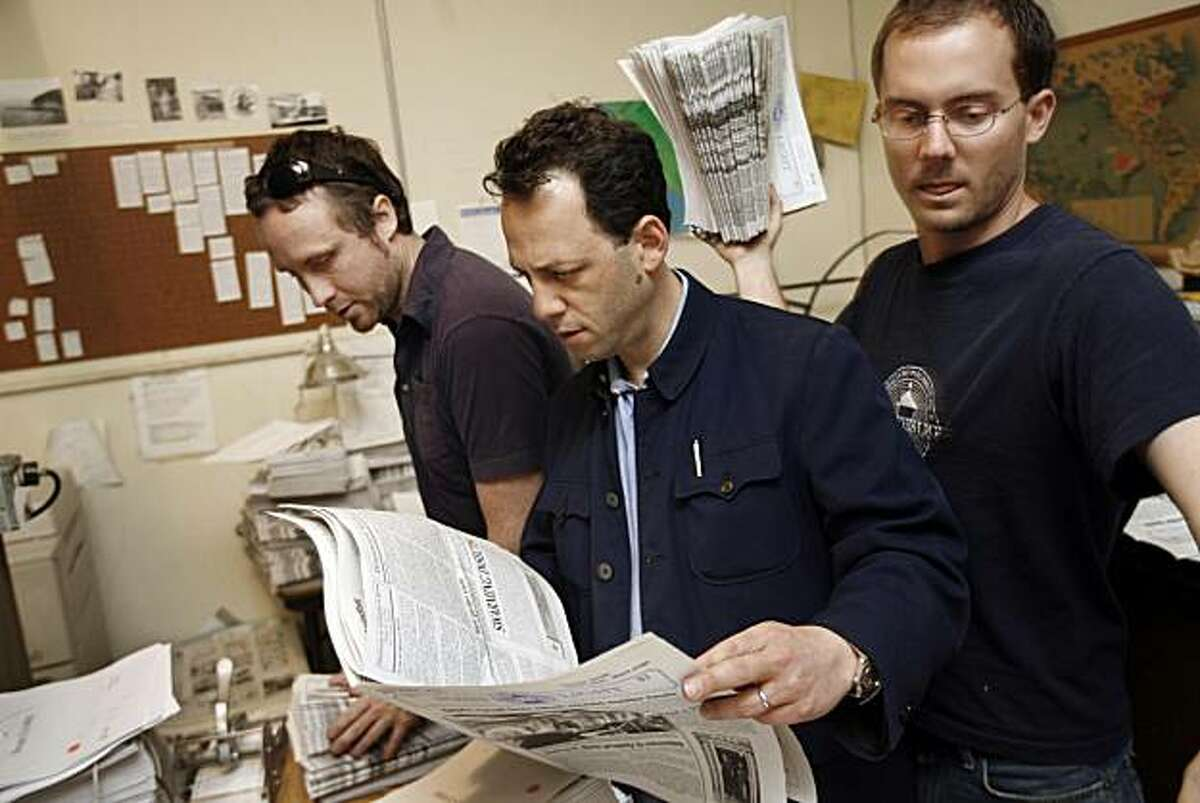 """Robert Plotkin (center), editor and publisher of the Point Reyes Light, goes over the latest issue - just off the press. Working along side him are David D. Jenkins (left), production, paste up and """"paper boy"""" and Peter Jamison, who among other responsibilities, is a reporter for the paper. Plotkin bought the weekly newspaper last year."""