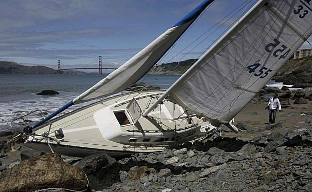 A reporter looks at a sailboat crashed along the rocks near China Beach in San Francisco on Monday. The Coast Guard says a married couple is dead after a weekend boating accident.