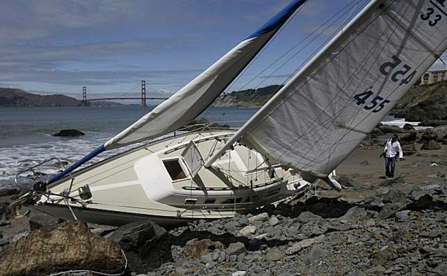 A reporter looks at a sailboat crashed along the rocks near China Beach in San Francisco on Monday. The Coast Guard says a married couple is dead after a weekend boating accident. Photo: Jeff Chiu, AP
