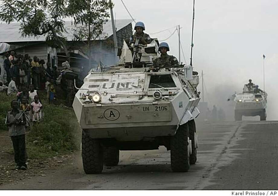 People stand by and look at United Nations armoured vehicles as they patrol in the streets of Goma in eastern Congo, Thursday, Oct. 30, 2008.  The Governor of Goma, Julien Mpaluku, acknowledged Wednesday that panic was spreading, but stressed that U.N. peacekeepers were still in charge and rebels had not yet entered the city.(AP Photo/Karel Prinsloo) Photo: Karel Prinsloo, AP