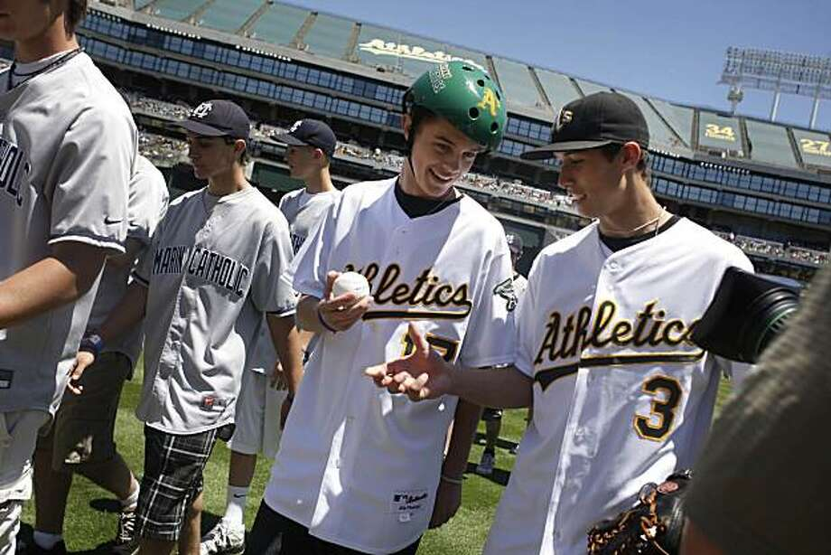 Zac Byers (in baseball cap at right) hands Gunnar Sandberg (in green helmet) the ball that Sandberg threw out for the first pitch and Byers caught at the McAfee Coliseum on Sunday May 23, 2010. Photo: Lea Suzuki, The Chronicle