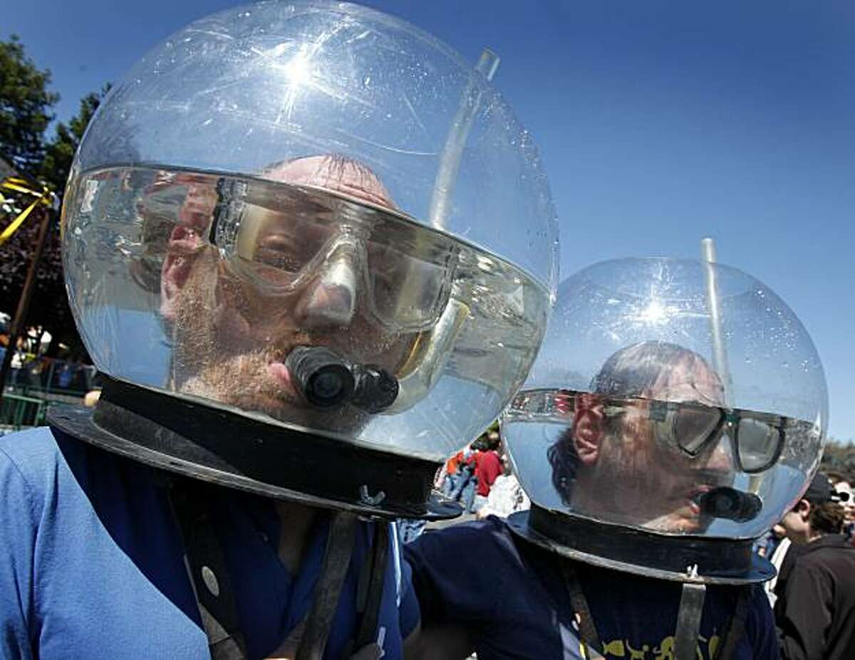 Charlie Getter (left) and Marque Cornblatt have some fun with their Waterboy helmets as they watch the crowd at the annual Maker Faire, a spectacle of ingenious inventions and gadgets Sunday at the San Mateo County Event Center.