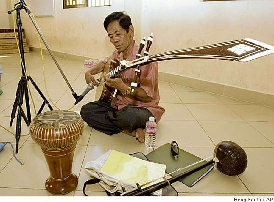 ** FILE ** In this Jan. 17, 2007 file photo, Cambodian musician plays traditional Cambodian instruments music for an opera at a rehearsal room in Phnom Penh, Cambodia.  Cambodia's first rock opera will make its world premiere in Phnom Penh next month, a cultural milestone in the Southeast Asian country where performing arts were banned during the brutal Khmer Rouge years.  Organizers said Wednesday, Oct. 29, 2008,  the show will open a 10-day run Nov. 28 in a converted movie theater in the capital, Phnom Penh, a year later than its planned debut at the end of 2007. (AP Photo/Heng Sinith, FILE) Photo: Heng Sinith, AP