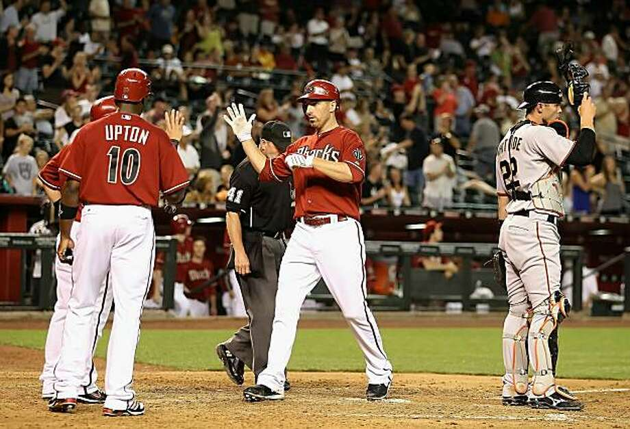 PHOENIX - MAY 19:  Adam LaRoche #25 of the Arizona Diamondbacks is congratulated by teammate Justin Upton #10 after hitting a 3 run home run against the San Francisco Giants during the eighth inning of the Major League Baseball game at Chase Field on May19, 2010 in Phoenix, Arizona. The Diamondbacks defeated the Giants 13-1. Photo: Christian Petersen, Getty Images