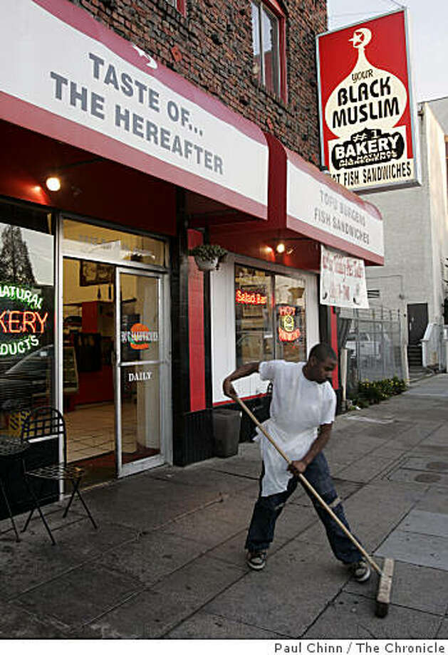 A unidentified employee (who would not give his name out to the media) sweeps the sidewalk in front of the Your Black Muslim Bakery shop after police officials announce the arrest of two men, including Yusef Bey IV, in connection with the vandalism of a liquor store in Oakland, Calif. on 11/29/05. Photo: Paul Chinn, The Chronicle