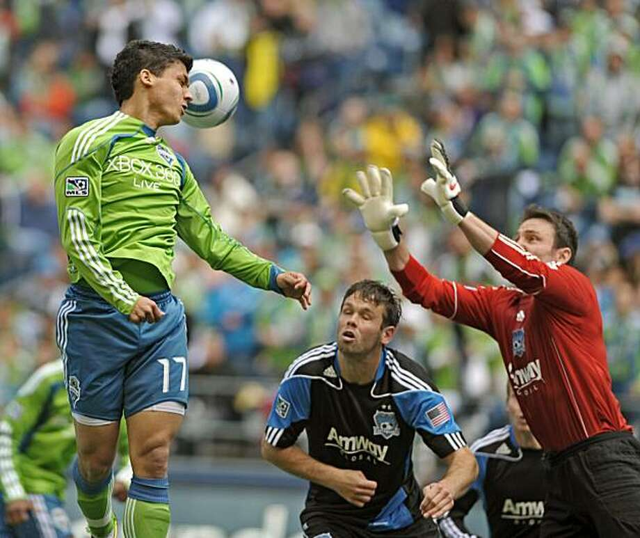 Seattle Sounfers Fredy Montero attempts a header in front of the goal of San Jose Earthquakes goalkeeper Joe Cannon, right during the second half of an MLS soccer game on Saturday May 22, 2010 at Qwest Field in Seattle. Photo: Peter Haley, AP