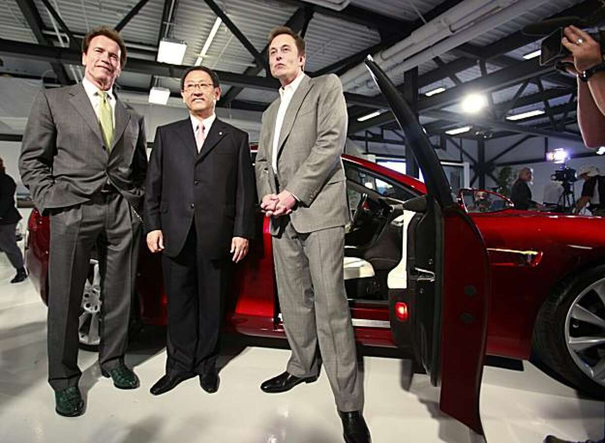 From left, Calif. Gov. Arnold Schwarzenegger, Toyota CEO Akio Toyoda, and Tesla CEO Elon Musk pose in front of a Tesla Model S at Tesla headquarters in Palo Alto, Calif., Thursday, May 20, 2010. Tesla will partner with Toyota Motors Corp. to build electric cars at a recently shuttered auto plant in the San Francisco Bay area.