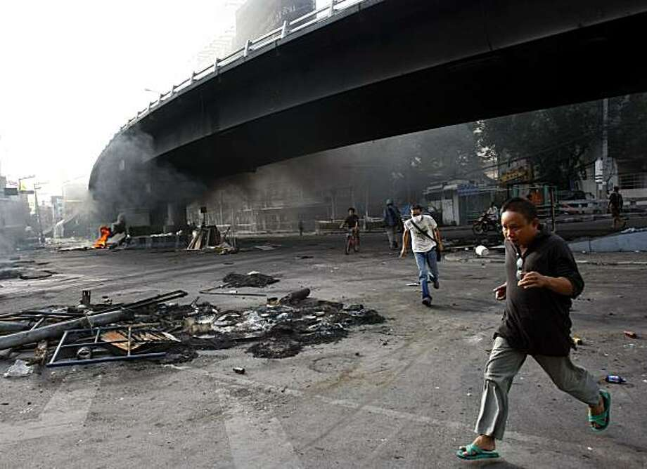 An anti-government protester runs for cover Tuesday, May 18, 2010 in Bangkok, Thailand. The Thai government rejected a proposal Tuesday for peace talks with leaders of the Red Shirt protesters to end the deadly mayhem gripping Bangkok, saying negotiationscannot start until the protesters disperse. Photo: Wason Wanichakorn, Associated Press