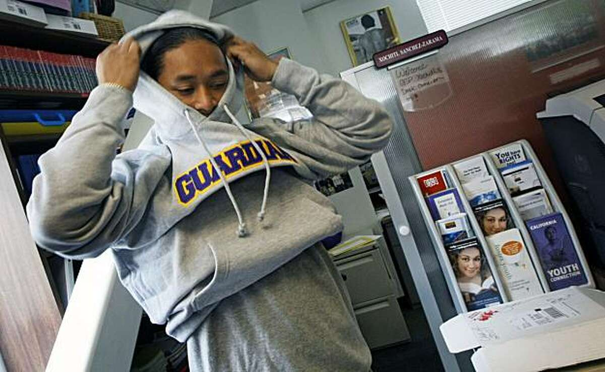 Sokhom Mao tries on a graduation gift, a sweatshirt from the Guardian Scholars program that proclaims his graduation from San Francisco State Tuesday May 18, 2010. Mao a former foster child did it with the help of the Guardian Scholars program.