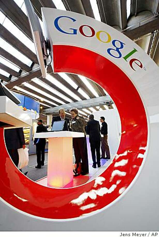 **FILE** In this Oct. 11, 2007 file photo, visitors look at an information screen at the Google Book Search stand at the International Frankfurt Book Fair 'Frankfurter Buchmesse' in Frankfurt, Germany. A settlement has been reached Tuesday, Oct. 28, 2008, in the lawsuit against Google over the Internet search engine's use of copyrighted material. (AP Photo/Jens Meyer, file) Photo: Jens Meyer, AP