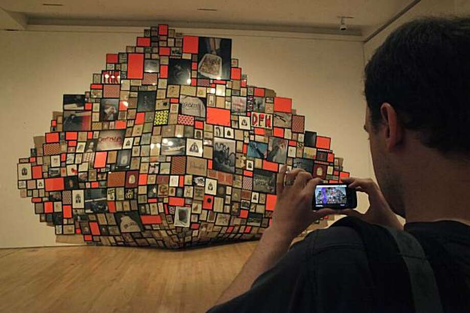 "Google publicist Jason Friedenfelds, takes a photo of Barry McGee's ""Untitled"", 1996/2009 Mixed media, while demonstrating how Google Goggles scans an image taken on a phone and uses a visual search, creating algorithms that can identify the subject of images with increasing accuracy,  to deliver relevant information on it at the San Francisco Museum of Modern Art in San Francisco, Calif. on Wednesday May 12, 2010. Photo: Lea Suzuki, The Chronicle"