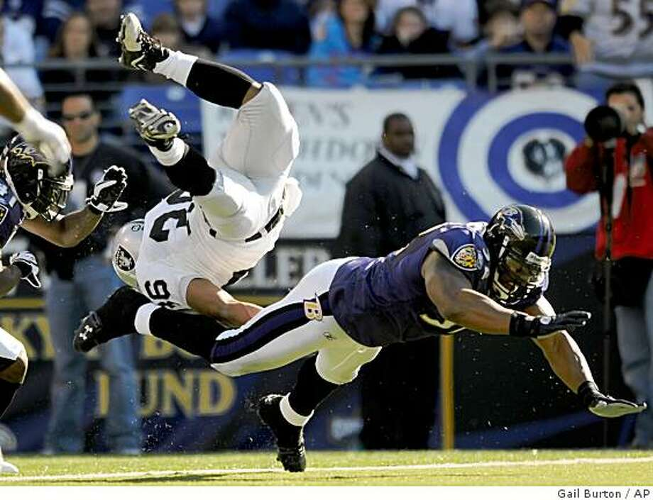 Oakland Raiders fullback Justin Griffith scores a touchdown after being hit by Baltimore Ravens' Ray Lewis, right, during the second half on Sunday, Oct. 26, 2008, in Baltimore. The Ravens won 29-10. Photo: Gail Burton, AP