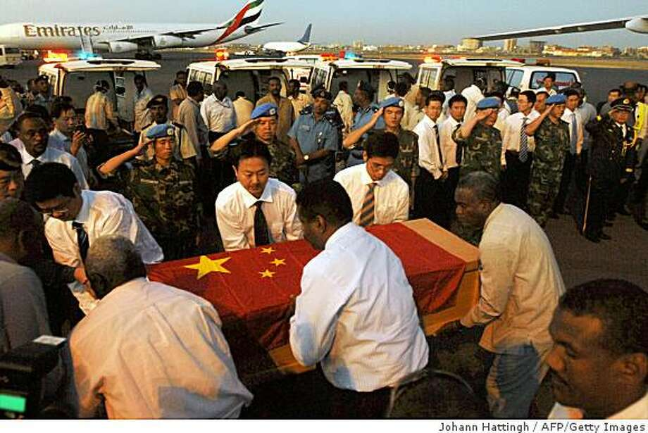 A handout picture from the United Nations Mission in Sudan (UNMIS) shows Chinese and Sudanese oil workers carrying a coffin of one of their kidnaped and killed colleagues ahead of repatriation in Khartoum airport on October 28, 2008. The bodies of three Chinese oil workers and three of their colleagues wounded in a kidnapping ordeal arrived in Khartoum today for full military honours. The killings, the first in a foreign hostage ordeal in Sudan in recent memory, has embarrassed the government, which has vowed to boost security for the country's crucial oil industry. AFP PHOTO/HO/UNMIS/Johann Hattingh  == RESTRICTED TO EDITORIAL USE == (Photo credit should read JOHANN HATTINGH/AFP/Getty Images) Photo: Johann Hattingh, AFP/Getty Images