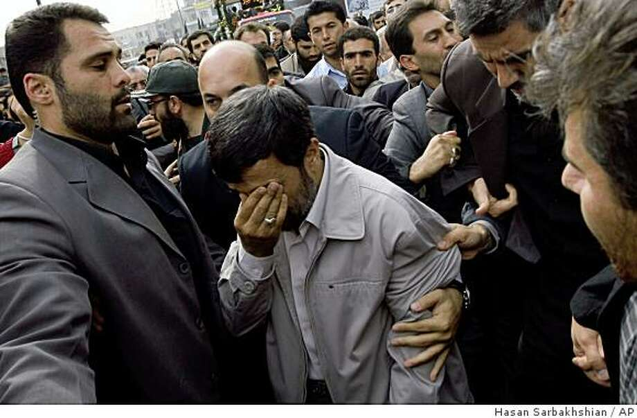 Surrounded by his bodyguards, Iranian President Mahmoud Ahmadinejad, center, wipes away a tear during a religious ceremony marking the death of the Shiite Saint Jaafar Sadeq in Tehran on Saturday Oct. 25, 2008. The world's 120 million Shiites venerate the sixth imam, or spiritual successor to the Prophet Muhammad, of the Shi'ite branch of Islam and the last to be recognized as imam by all the Shi'ite sects. Theologically, he advocated a limited predestination and proclaimed that Hadith (traditional sayings of the Prophet), if contrary to the Qur'an, should be rejected. (AP photo/Hasan Sarbakhshian) Photo: Hasan Sarbakhshian, AP