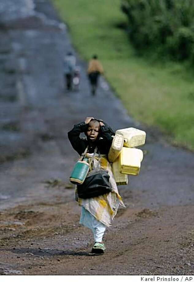 A young girl carries her belongings as she flees fighting, Sunday, Oct. 26, 2008 near Kibumba some 40 kilometers north of Goma in eastern Congo. Rebels loyal to renegade Gen. Laurent Nkunba have seized a major army camp in eastern Congo in heavy fighting Sunday that sent thousands of civilians fleeing, U.N. officials and rebels said.(AP Photo/Karel Prinsloo) Photo: Karel Prinsloo, AP