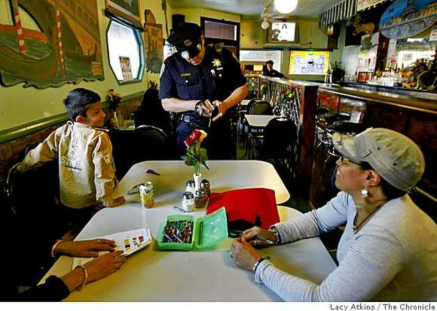 Officer John Cathey looks for stickers to give to Tegjot Dhaliwal at a pizzeria along 24th street, Wednesday Oct. 22, 2008,  in San Francisco, Calif. Officer Cathey is on foot patrol along 24th street and believes the gang injunction has  helped families feel safer. Photo: Lacy Atkins, The Chronicle
