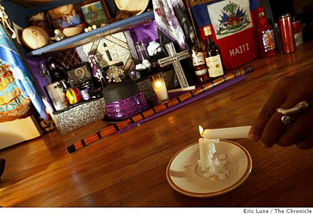 Portsha Jefferson lights a candle in front of her altar which celebrates the Haitian All Hallows Eve.