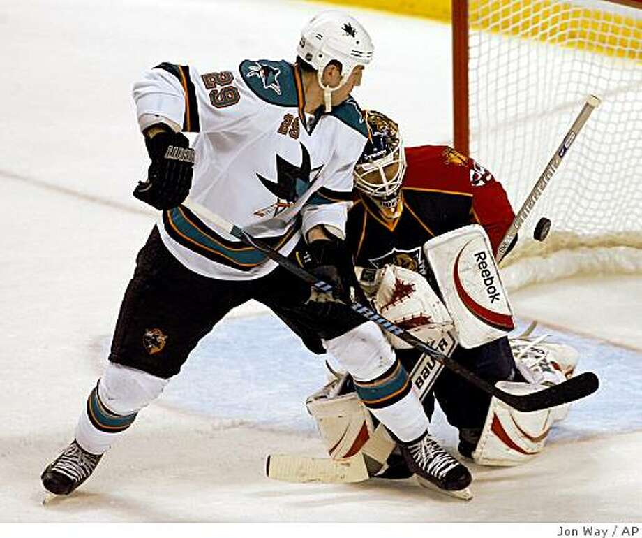 Florida Panthers goalie Thomas Vokoun, right, of the Czech Republic, deflects a shot by San Jose Sharks' Ryan Clowe (29) in the third period of a NHL hockey game in Sunrise, Fla., Friday, Oct. 24, 2008. The Panthers won 4-3. (AP Photo/Jon Way) Photo: Jon Way, AP