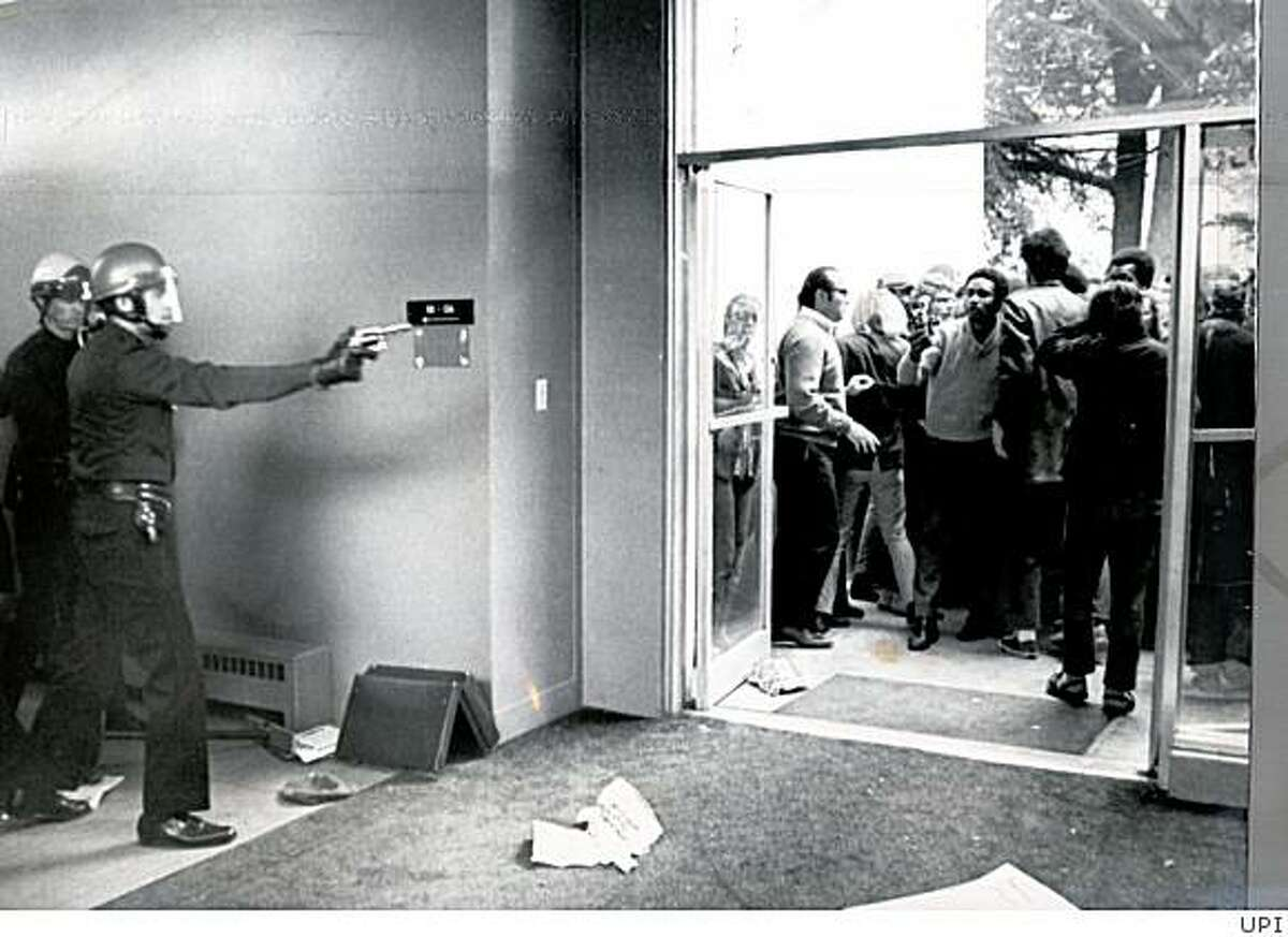 Policeman with drawn revolvers keep protesters at bay from the administration building at San Francisco State on December 5, 1968.