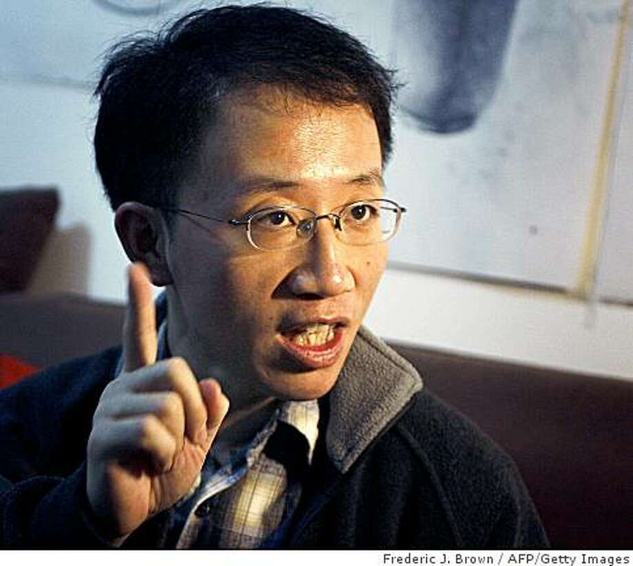 "(FILES) This photo takenon January 9, 2007 shows human rights activists Hu Jia speaking while under house arrest in Beijing. Chinese dissident Hu Jia won the European Parliament's prestigious Sakharov Prize on October 23, 2008. Greens bloc officials said, amid accusations that Beijing had pressured lawmakers not to give it to him. ""Awarding the Sakharov to Hu Jia is a reflection of this very spirit of this prize, which supports free thought and honours human rights defenders fighting repression,"" Greens leaders Daniel Cohn-Bendit and Monica Frassoni said.   AFP PHOTO / Frederic J. BROWN / FILES (Photo credit should read FREDERIC J. BROWN/AFP/Getty Images) Photo: Frederic J. Brown, AFP/Getty Images"